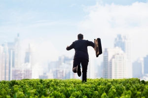 Businessman running towards city with briefcase in green field